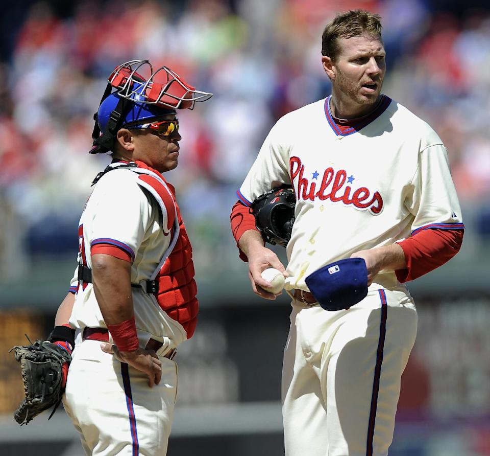 Philadelphia Phillies' Roy Halladay, right, and Carlos Ruiz wait for the results of a review of a home run by Miami Marlins' Adeiny Hechavarria in the third inning of a baseball game on Sunday, May 5, 2013, in Philadelphia. (AP Photo/Michael Perez)
