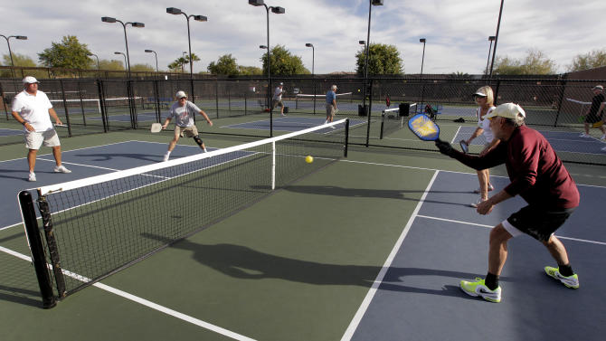 """In this Monday, Dec. 3, 2012 photo, clockwise from left; Gary Dyson, Del Teter, Donna Shattenberg and David Bone compete in a game of pickleball at Sun City West senior community in Surprise, Ariz. A hybrid of tennis, badminton and table tennis, pickleball is played on a court a quarter the size of a tennis court, with hard rackets and a variety of whiffle ball. """"It's really easy to learn, it's a lot of fun and it's a very social game because you're in a small area with a lot of interaction,"""" said Bill Booth, president of the USA Pickleball Association.  (AP Photo/Matt York)"""
