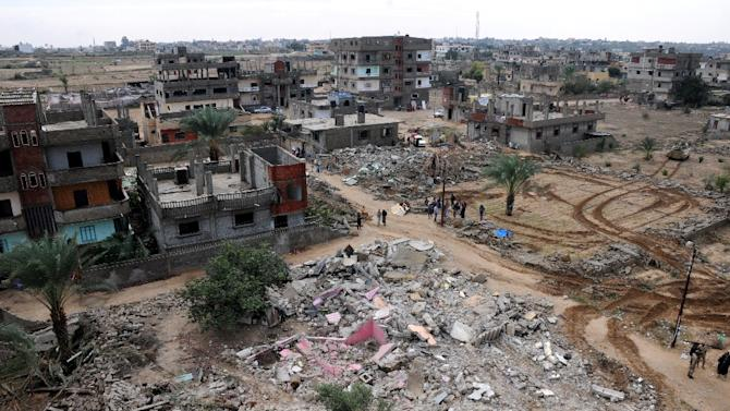 Residents gather next to the remains of buildings destroyed by the Egyptian military in divided border town of Rafah, along the border with the Hamas-run Gaza Strip,  on November 4, 2014