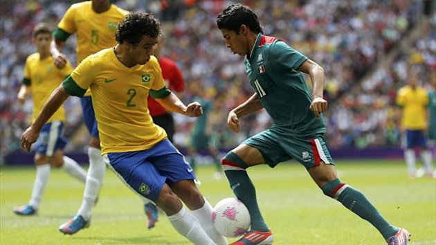 Mexico's Javier Aquino (R) challenges Brazil's Rafael during their men's football gold medal match
