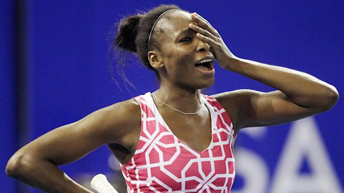 Venus Williams of the U.S. reacts after a dropping a point against her sister Serena during an exhibition tennis match at Ellis Park Indoor Arena in Johannesburg, South Africa, Sunday, Nov. 4, 2012. (AP Photo/Themba Hadebe)