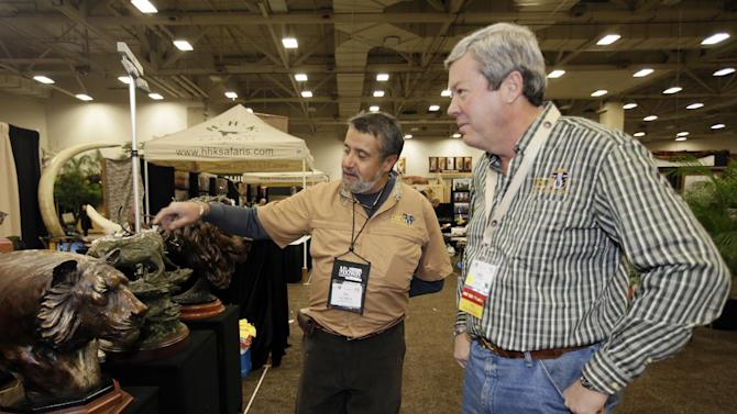 Dallas Safari Club executive director Ben Carter, right, talks with wildlife artist Raj S. Paul at his exhibit booth in the Dallas Convention Center as preparations continue for the clubs weekend show, Wednesday, Jan. 8, 2014, in Dallas. The FBI is investigating death threats made against members of the Dallas Safari Club, which intends to auction off a rare permit to hunt an endangered black rhino, an FBI spokeswoman said Wednesday. (AP Photo/Tony Gutierrez)