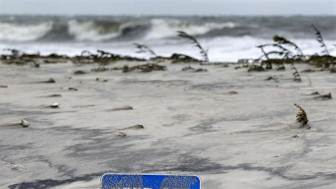 A keep off the dunes sign is buried Tuesday morning, Oct. 29, 2012, in Cape May, N.J., after a storm surge from superstormSandy pushed the Atlantic Ocean over the beach and into the streets. The storm that made landfall in New Jersey on Monday evening with 80 mph sustained winds killed at least 16 people in seven states, cut power to more than 7.4 million homes and businesses from the Carolinas to Ohio, caused scares at two nuclear power plants and stopped the presidential campaign cold. (AP Photo/Mel Evans)