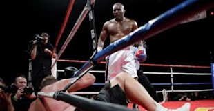 Evander Holyfield of the U.S. stands over Francois Botha of South Africa after knocking down Botha in the eighth round of their heavyweight bout at the Thomas & Mack Center in Las Vegas - 0