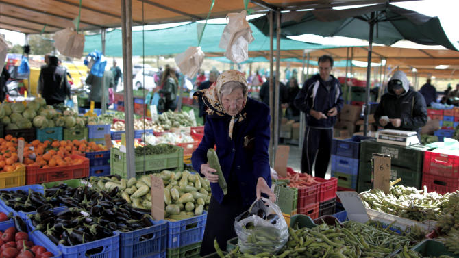 A elderly woman buys goods from a vegetable market, in central Nicosia, on Saturday, March 23, 2013. Politicians in Cyprus were racing Saturday to complete an alternative plan raising funds necessary for the country to qualify for and international bailout, with a potential bankruptcy just three days away. (AP Photo/Petros Giannakouris)