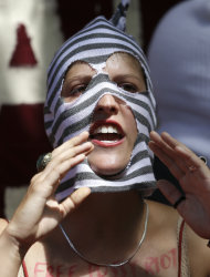A Supporter of the Russian punk rock band Pussy Riot protests outside the Russian Embassy in London, Friday, Aug. 17, 2012, as the verdict in their case is announced in Moscow. A Russian judge found three members of the provocative punk band Pussy Riot guilty of hooliganism on Friday, in one of the most closely watched cases in recent Russian history. The judge said the three band members committed hooliganism driven by religious hatred and offending religious believers. The three were arrested in March after a guerrilla performance in Moscow's main cathedral calling for the Virgin Mary to protect Russia against Vladimir Putin, who was elected to a new term as Russia's president a few days later.(AP Photo/Alastair Grant)