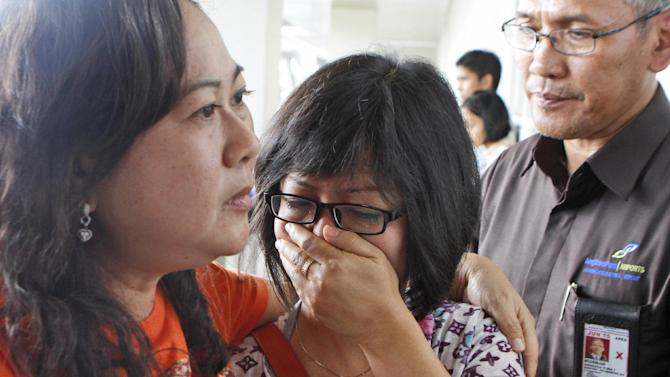 CORRECTS NUMBERS OF THE PASSENGERS - A relative of AirAsia flight QZ8501 passengers weeps as she waits for the latest news on the missing jetliner at Juanda International Airport in Surabaya, East Java, Indonesia, Sunday, Dec. 28, 2014. The AirAsia plane with 162 people on board lost contact with ground control on Sunday while flying over the Java Sea after taking off from the provincial city in Indonesia for Singapore. (AP Photo/Trisnadi)