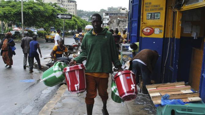 Man sells buckets used for washing hands on a street in downtown Monrovia