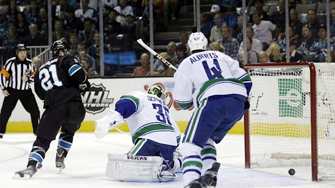 Vancouver Canucks goalie Cory Schneider, center, is beaten for a goal on a shot from San Jose Sharks defenseman Brent Burns as San Jose Sharks left wing T.J. Galiardi (21) and the Canucks' Andrew Alberts (41) watch during the first period of Game 4 of their first-round NHL hockey Stanley Cup playoff series in San Jose, Calif., Tuesday, May 7, 2013. (AP Photo/Marcio Jose Sanchez)