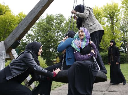 Yasmin pushes Hana on a swing after finishing a GCSE exam near their school in Hackney, east London