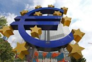 A giant Euro symbol outside the European Central Bank in Frankfurt. Construction cranes on the site of the new Raiffeisen building to be completed in Vienna