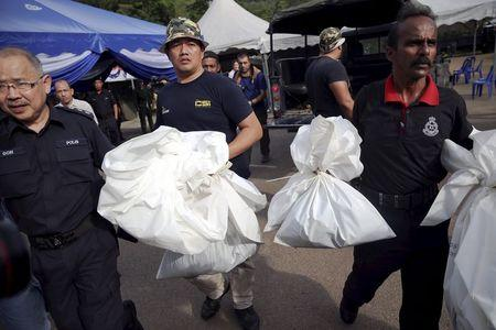 Forensic policemen carry body bags with human remains found at the site of human trafficking camps in the jungle close the Thailand border after they brought them to a police camp near Wang Kelian in northern Malaysia