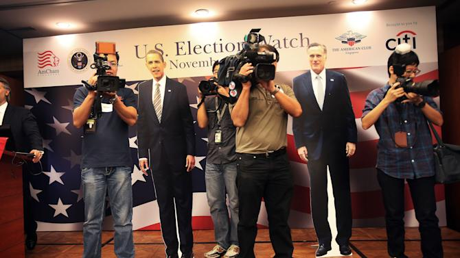 TV cameramen and photographers stand on stage with cutouts of U.S. Presidential candidates, Mitt Romney, right, and Barack Obama, as Americans and supporters gather at the American Club in Singapore to watch the live coverage of the election Wednesday, Nov. 7, 2012. (AP Photo/Wong Maye-E)