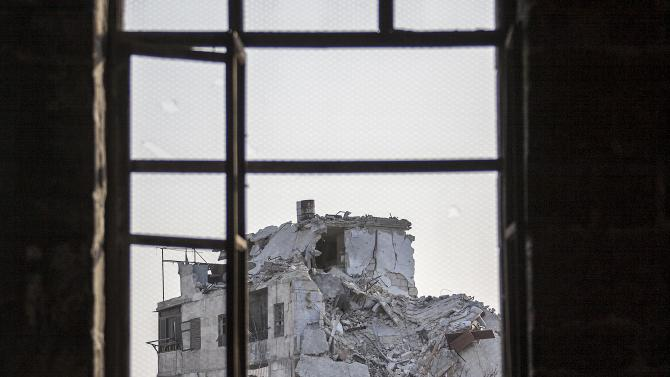 In this Sunday, Nov. 04, 2012 photo, a damaged building is seen through a window  after several weeks of intense battles between rebel fighters and the Syrian army in the Jedida district of Aleppo, Syria. The uprising against President Bashar Assad started with peaceful demonstrations in March last year, but has since morphed into a bloody civil war. Activists say more than 36,000 people have been killed in 19 months of fighting. (AP Photo/Narciso Contreras)