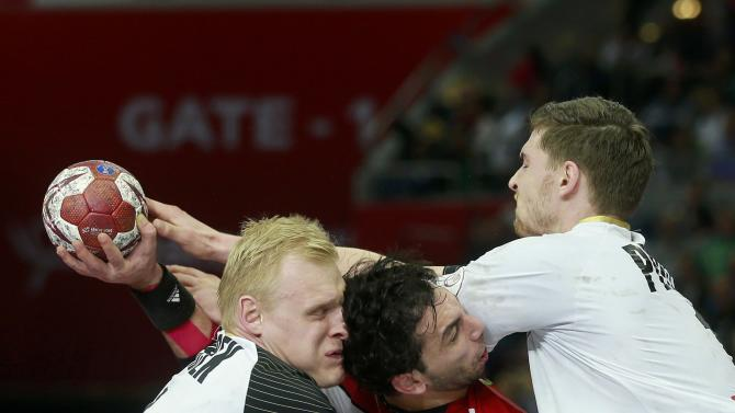 Elahmar of Egypt is challenged by Wiencek and Pekeler of Germany during their round of 16 match of the 24th men's handball World Championship in Doha