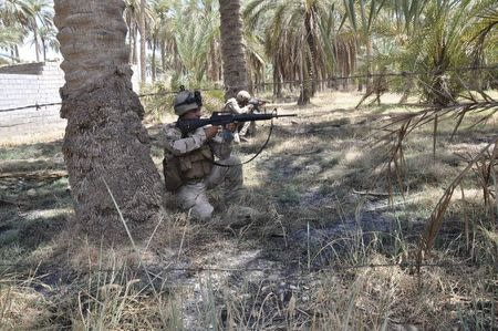 Members of the Iraqi security forces take their positions during a patrol in the town of Jurf al-Sakhar