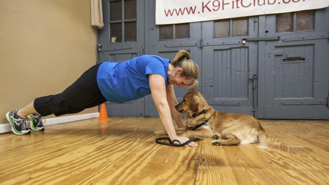 In this Feb. 14, 2013 photo, Cindy Rodkin, a member of the K9 Fit Club, works out with her golden retriever, Khaki, looking on during a class held in Chicago. Rodkin has lost 41 pounds since joining the K9 Fit Club in September 2012. (AP Photo/Teresa Crawford)