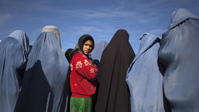 Afghan girl stands among widows clad in burqas during cash for work project by humanitarian organisation CARE International in Kabul