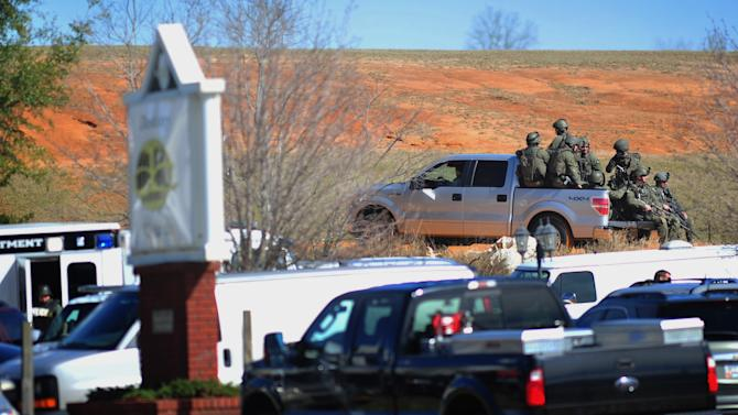 Law enforcement personnel in tactical gear ride a pickup to the scene of an ongoing hostage crisis on Friday, Feb. 1, 2013 below the site where Tuesday's school bus shooting suspect is barricaded in a bunker holding a five-year-old boy captive. More than three days after authorities said a gunman shot a school bus driver dead, grabbed a kindergartner and slipped into an underground bunker, the man showed no signs Friday of turning himself over to police. (AP Photo/The Dothan Eagle, Jay Hare)