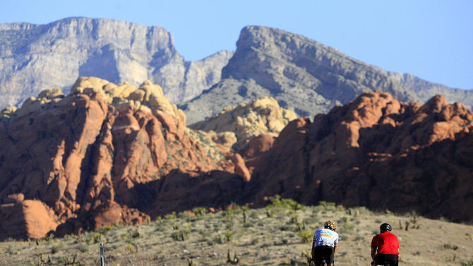 FILE - This May 6, 2006 file photo shows two cyclists riding along the 13-mile-long scenic drive at Red Rock Canyon National Conservation Area in Nevada. These towering red sandstone cliffs, some reaching 3,000 feet, is just 15 miles west of metropolitan Las Vegas. (AP Photo/Jae C. Hong, file)