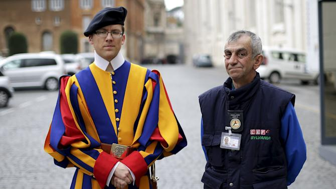 Roberto, a homeless man who lives around Vatican, poses with a Swiss guard before entering the Vatican