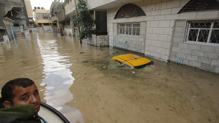 A car is seen submerged in floodwaters after heavy rains on a stormy day in Gaza City