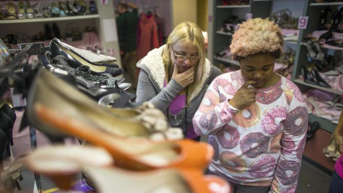 Grant chooses shoes with volunteer Solo at an event that provides free prom dresses, shoes and accessories to 70 homeless and low income school girls from the Assistance League of Los Angeles in Los Angeles