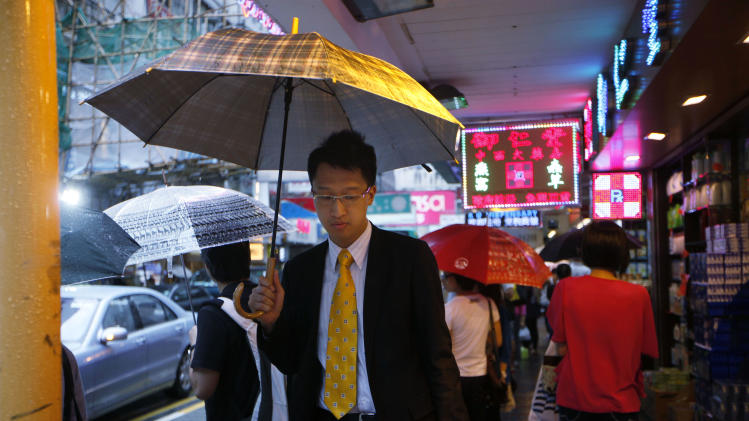 People walk in the rain at a shopping district in Hong Kong Thursday, July 26, 2012. Asian stock markets rose Thursday amid hopes Europe will give its bailout fund more financial firepower but gains were tempered as South Korea reported its economic growth slowed to a two-year low. (AP Photo/Kin Cheung)
