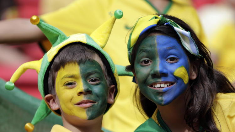 Young fans pose for a photograph prior to the group A World Cup soccer match between Cameroon and Brazil at the Estadio Nacional in Brasilia, Brazil, Monday, June 23, 2014