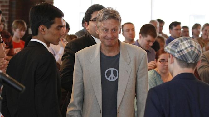 In this Sept. 21, 2012 photo, Libertarian Party presidential nominee Gary Johnson, right, greets  students at Macalester College in St. Paul, Minn.  Third-party candidates Johnson and Virgil Goode are blips in the presidential race. They have little money, aren't on stage for presidential debates and barely register in the polls _ when survey takers even bother to list them as options.(AP Photo/Jim Mone, File)
