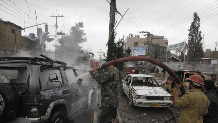 Firefighters spray extinguish fire on burning vehicles at site of a bomb attack in Quetta