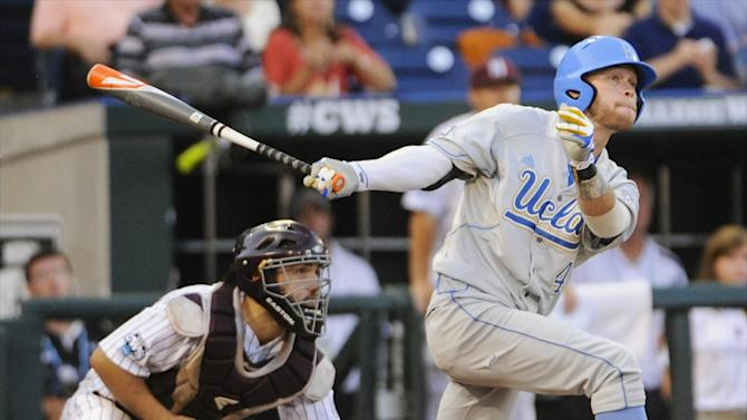 UCLA's Eric Filia follows his two-RBI single to right field with Mississippi State catcher Nick Ammirati, left, in the fourth inning of Game 1 in their NCAA College World Series baseball finals, Monday, June 24, 2013, in Omaha, Neb. UCLA's Brian Carroll and Brenton Allen scored on the play. (AP Photo/Francis Gardler)