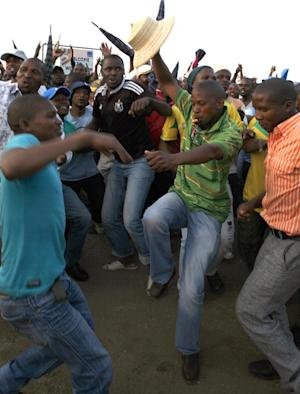 Miners sing and dance after accepting a pay rise in Lonmin Platinum Mine near Rustenburg, South Africa, Tuesday, Sept. 18, 2012. Striking miners have accepted a company offer of a 22% overall pay increase to end more than five weeks of crippling and bloody industrial action. (AP Photo/Themba Hadebe)