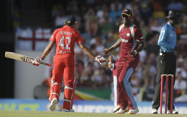 West Indies' Darren Sammy, right, smiles to England's Ravi Bopara during their first T20 International cricket match at the Kensington Oval in Bridgetown, Barbados, Sunday, March 9, 2014. (AP