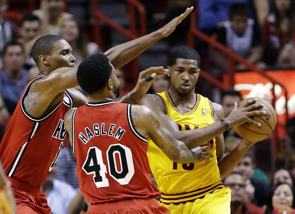 Cleveland Cavaliers forward Tristan Thompson, right, looks for an opening past Miami Heat center Chris Bosh, left, and forward Udonis Haslem (40) during the first half of an NBA basketball game, Sunday, Feb. 24, 2013, in Miami. (AP Photo/Wilfredo Lee)