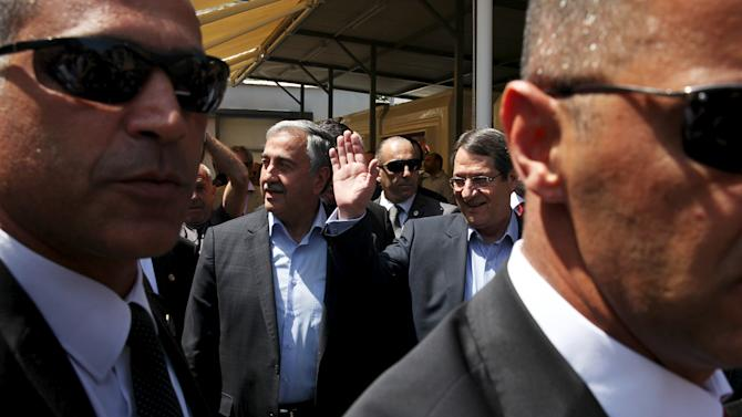 Turkish Cypriot leader Mustafa Akinci (centre L) and Greek Cypriot leader, Cypriot President Nicos Anastasiades, take a stroll through old Nicosia while guards look on