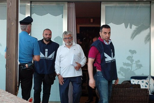 <p>Italian anti-mafia police flank Giuseppe Mandara (centre) after his arrest near Naples. Mandara is the head of the biggest buffalo mozzarella manufacturing company in Italy.</p>