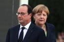 France's President Francois Hollande, left, and German Chancellor Angela Merkel, during a remembrance ceremony to mark the centenary of the battle of Verdun, at the Douaumont memorial, northeastern France, Sunday May 29, 2016. In solemn ceremonies Sunday in the forests of eastern France, French President Francois Hollande and German Chancellor Angela Merkel marked 100 years since the Battle of Verdun, determined to show that, despite the bloodbath of World War I, their countries' improbable friendship is now a source of hope for today's fractured Europe. (AP Photo/Thibault Camus)