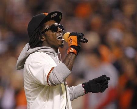 "Rapper Lil Wayne sings ""Take Me Out To The Ball Game"" during the seventh inning stretch in Game 6 of the MLB NLCS playoff baseball series between the St. Louis Cardinals and the San Francisco Giants in San Francisco, October 21, 2012. REUTERS/Robert Galbraith"