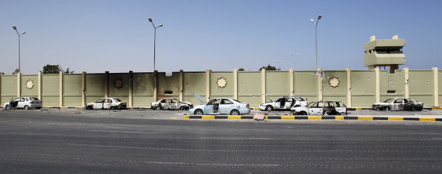 Destroyed and burned cars parked along the wall of Moammar Gadhafi's compound Bab al-Aziziya, in Tripoli, Libya, Friday, Aug. 26, 2011. (AP Photo/Francois Mori)