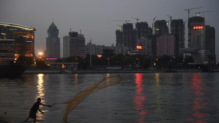 A man casts a net by the side of a river next to a construction site of new residential buildings in Wuhan
