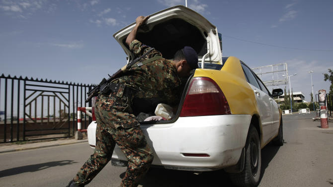 A policeman checks a car at the entrance of Sanaa International Airport, Wednesday, Aug. 7, 2013, in Yemen. Authorities foiled plots by al-Qaida to take over key cities in southern Yemen and attack strategic ports and gas facilities, a government spokesman said Wednesday amid a heightened alert that has seen Western embassies evacuated and a new suspected U.S. drone strike that killed seven alleged militants from the terrorist group. (AP Photo/Hani Mohammed)