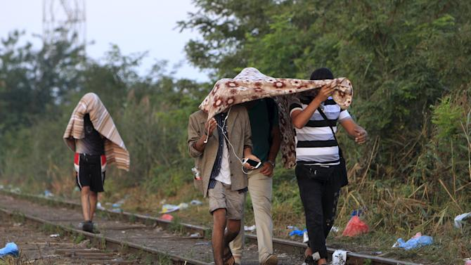 Migrants walk along a railway track after crossing into Hungary from the border with Serbia near Roszke, Hungary