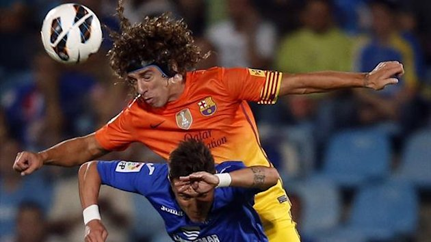 Barcelona's Carles Puyol (TOP) and Getafe's Adrian Colunga challenge for the ball during their Spanish first division soccer match at Coliseum Alfonso Perez stadium in Getafe, near Madrid (Reuters)