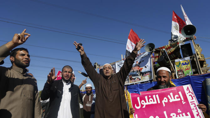 """Islamist protesters supporting Egyptian President Mohammed Morsi chant slogans in front of the Media City complex in Giza, Egypt, Wednesday, Dec. 12, 2012. The Arabic sign at right reads, """"journalist remnants will destroy Egypt."""" An Egyptian opposition alliance urged supporters on Wednesday to vote """"No"""" in the referendum on a disputed constitution but said it may still boycott if its conditions are not met.(AP Photo/Petr David Josek)"""
