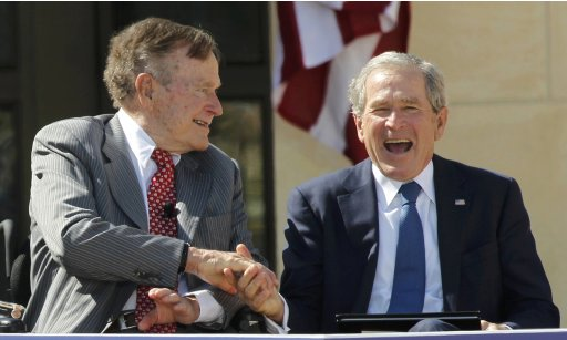 US Presidents George H.W. Bush and George W. Bush,shake hands at the dedication for the George W. Bush Presidential Center in Texas