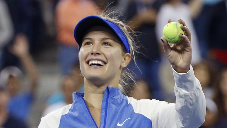 Bouchard of Canada celebrates by hitting balls into the crowd after defeating Cirstea of Romania during their women's singles match at the U.S. Open tennis tournament in New York
