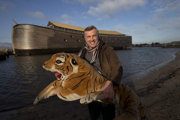 Johan Huibers poses with a stuffed tiger in front of the full scale replica of Noah's Ark after being asked by a photographer to go outside with the animal in Dordrecht, Netherlands, Monday Dec. 10, 2012. The Ark has opened its doors in the Netherlands after receiving permission to receive up to 3,000 visitors per day. For those who don't know or remember the Biblical story, God ordered Noah to build a boat massive enough to save animals and humanity while God destroyed the rest of the earth in an enormous flood. (AP Photo/Peter Dejong)