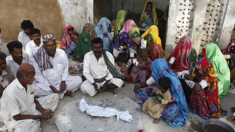 Family members and villagers gather around the body of two-month-old Mangal, who died of infection, before his burial in a drought-stricken area of Kaposar village of Mithi, in the Sindh province