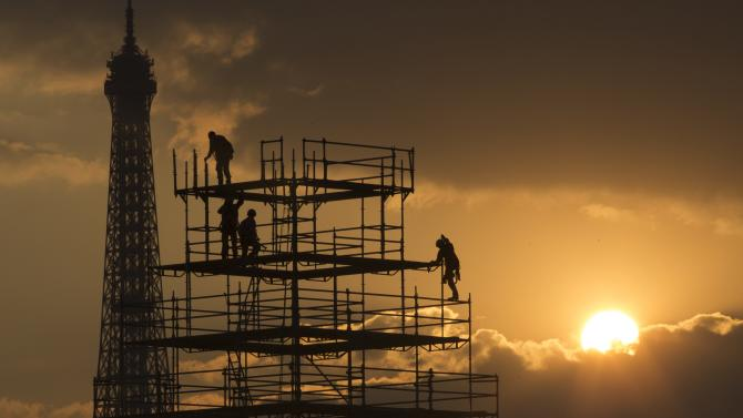 Workers are seen in silhouette, along with the Eiffel Tower, as they construct scaffolding on the Place de la Concorde as the sun sets on an autumn day in Paris